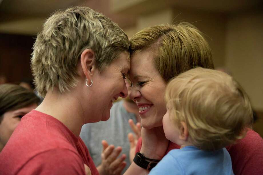 Kori Ashton, left and Becky Ashton put their heads together  while their son Andy Ashton watches after getting married at the Bexar County Courthouse in San Antonio, Texas on June 26, 2015.  They got married in Iowa five years ago, but wanted their marriage to be recognized in Texas.  Their fifth anniversary was last week. Photo: Carolyn Van Houten, Staff / San Antonio Express-News / 2015 San Antonio Express-News