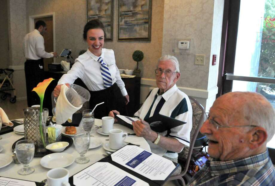 Server Leanne Bentley, left, refills Beltrone residents Dan Ryan and Eli Swartz's water glasses during the PRIME Life restaurant opening Wednesday, June 24, 2015, in the Beltrone Living Center Lakeview Dining Room in Colonie, N.Y. (Phoebe Sheehan/Special to The Times Union) Photo: PS / 00032374A