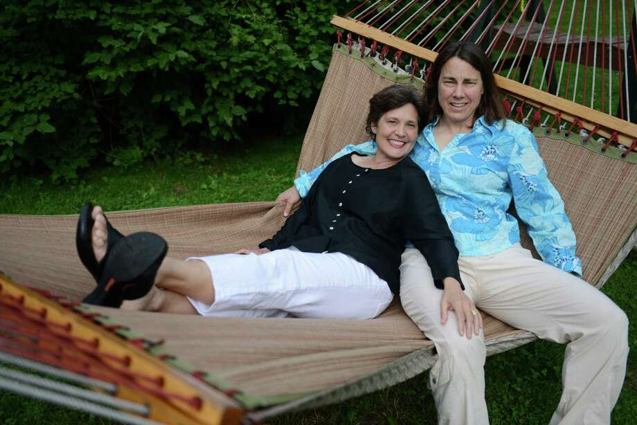 Robin Howell, left, and Deb Neumayer, relax on a hammock outside their home in Danbury, Conn. on Wednesday, June 26, 2013.  Howell and Neumayer have been together for 25 years and married for five years.  The U.S. Supreme Court ruled Wednesday in a 5-4 decision to strike down the Defense of Marriage Act, which defined marriage as between a man and a woman. Photo: Tyler Sizemore / Tyler Sizemore / The News-Times