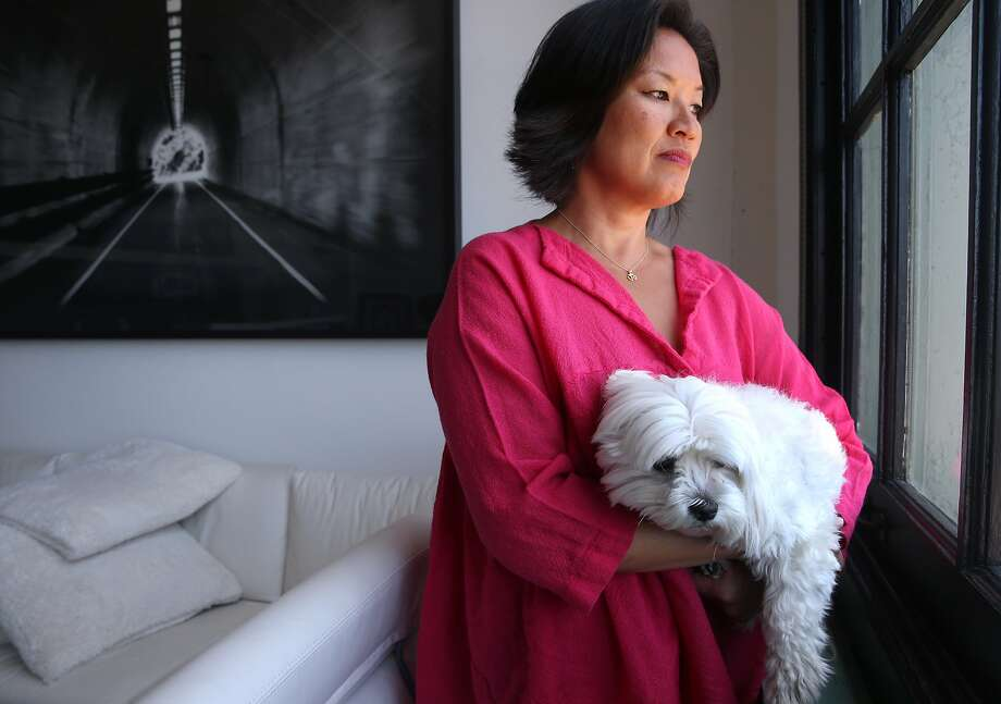 Mimi Lee holds her dog Toshi at her loft in San Francisco, Calif. on Friday, June 26, 2015. Just days before her wedding in 2010, Lee was diagnosed with breast cancer so she and her new husband agreed to in vitro fertilization and freeze several embryos. After she finished her cancer treatments, her husband told her he wanted a divorce and has since refused to give Lee consent to use the frozen embryos for her last chance to have a biological child and instead, wants the embryos destroyed. Photo: Paul Chinn, The Chronicle
