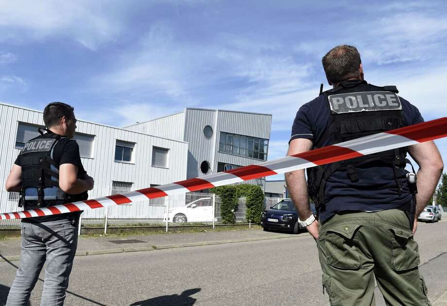 "French police officers stand guard near a cordon outside the Colicom delivery service company in Chassieu near Lyon on June 26, 2015, where the victim who was decapitated during the attack earlier in the day in Saint-Quentin-Fallavier worked. At least one suspected Islamist launched a daylight raid on an industrial gas factory in France and pinned a severed head to the gates, in what President Francois Hollande called a ""terrorist"" attack. The head of the victim, who ran a delivery service, was found pinned to the gates at the American-owned Air Products factory. AFP PHOTO / PHILIPPE DESMAZESPHILIPPE DESMAZES/AFP/Getty Images Photo: PHILIPPE DESMAZES, Staff / AFP / Getty Images / AFP"