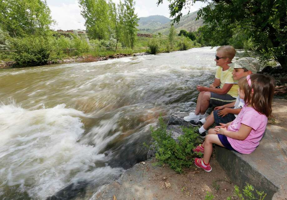 Carol Johnston sits with grandchildren Olivia and Anthony Villano as water rushes by in Clear Creek in Golden, Colo. Two suburban Denver counties have banned access to waterways. Photo: David Zalubowski /Associated Press / AP