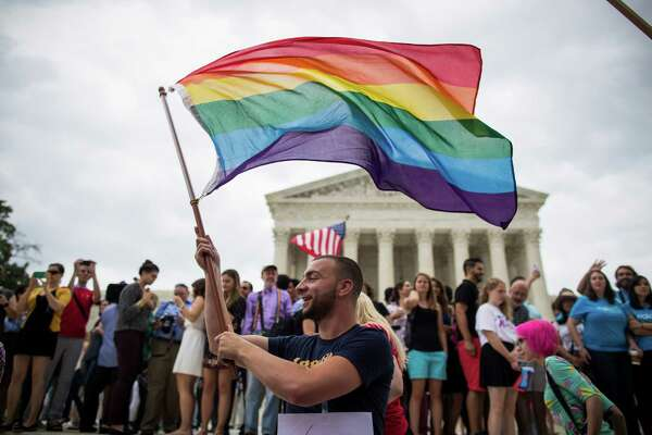 Vin Testa waves a rainbow flag outside of U.S. Supreme Court following the announcement of the ruling on the same-sex marriage case, in Washington, June 26, 2015. In a long-sought victory for the gay rights movement, the Supreme Court ruled Friday that the Constitution guarantees a nationwide right to same-sex marriage.  (Zach Gibson/The New York Times)