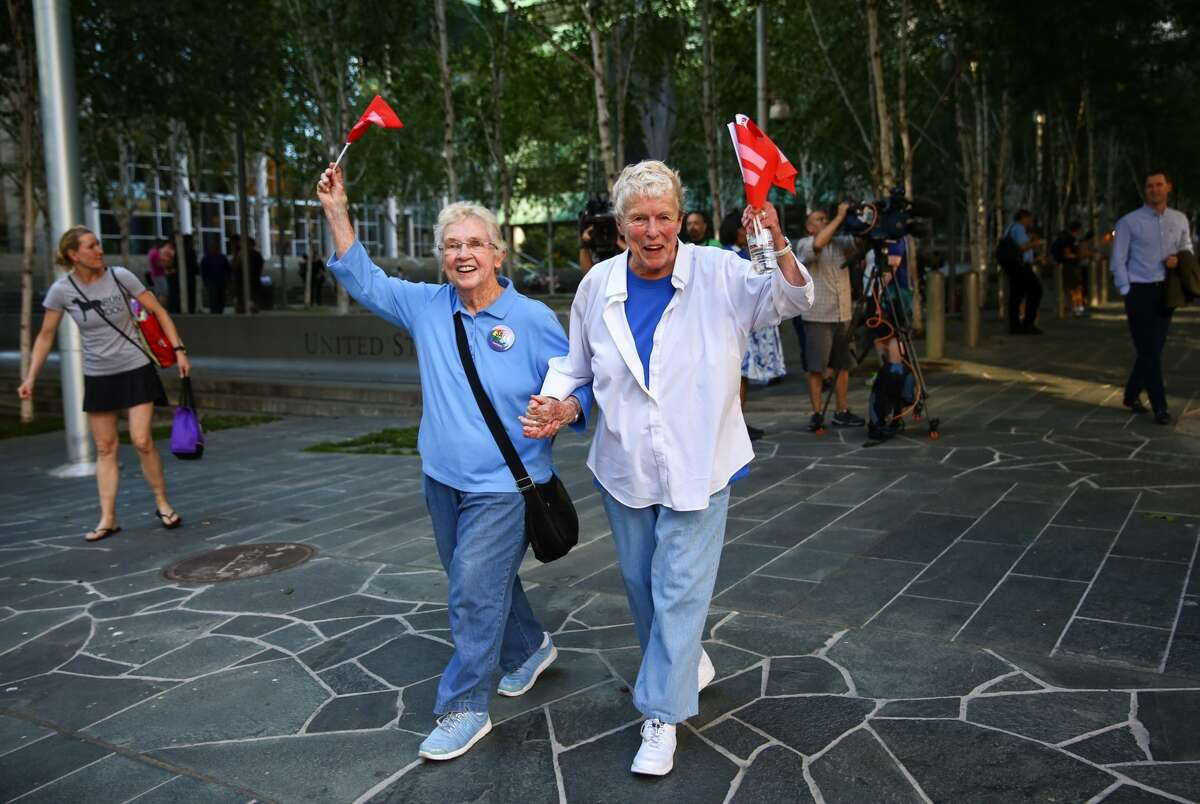 Pete-e Petersen and her wife Jane Abbott Lighty hold hands as they walk from a rally at the Federal Courthouse in Seattle on Friday, June 26, 2015.