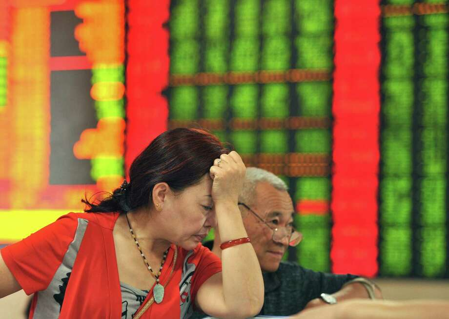 Investors react as they check stock prices in a brokerage house in Fuyang in China's Anhui province Friday. Chinese stocks plummeted as panicked investors rushed to sell over fears that an extended bull market was coming to an end.  Photo: STR / CHINATOPIX