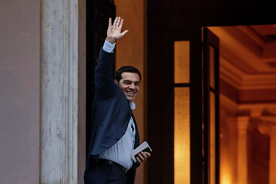 Greece's Prime Minister Alexis Tsipras waves and smiles as he arrives at Maximos Mansion in Athens, Friday, June 26, 2015. The bitter standoff between Greece and its international creditors was extended into the weekend, just days before Athens has to meet a crucial debt deadline which could decide whether it goes bankrupt and gets kicked out of the euro currency club.(AP Photo/Daniel Ochoa de Olza) Photo: Daniel Ochoa De Olza, STF / AP