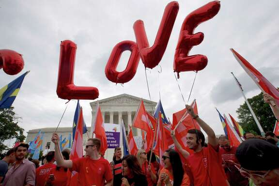"Balloons spell out the word ""love"" over the Supreme Court in Washington, Friday June 26, 2015, after the court declared that same-sex couples have a right to marry anywhere in the US.  (AP Photo/Jacquelyn Martin)"