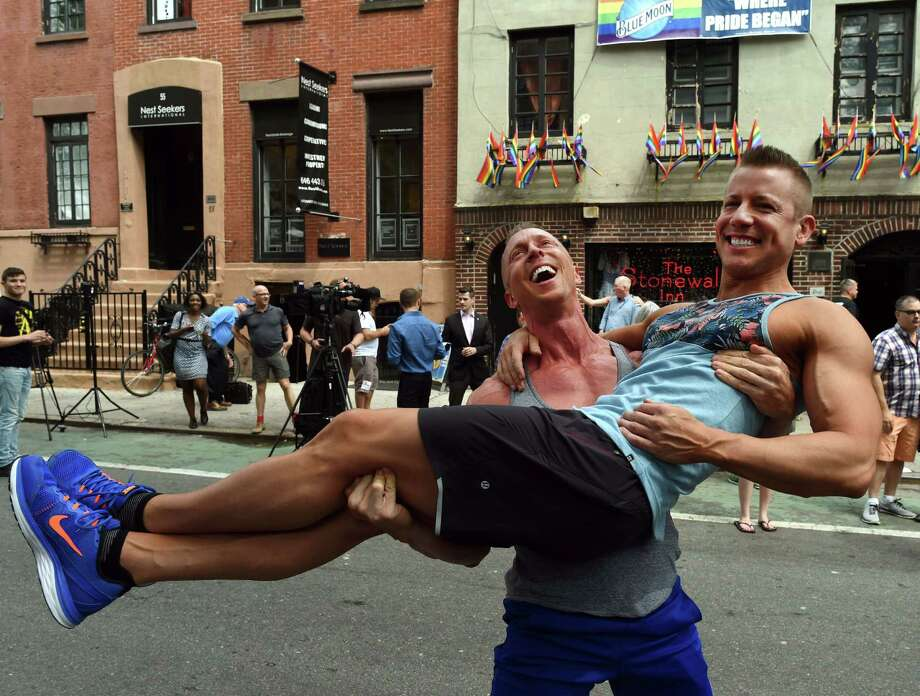 Justin Kattler and Tim Loecker from Dallas celebrate Friday's Supreme Court ruling on same-sex marriage outside the Stonewall Tavern in the West Village in New York City. Photo: TIMOTHY A. CLARY, Staff / AFP