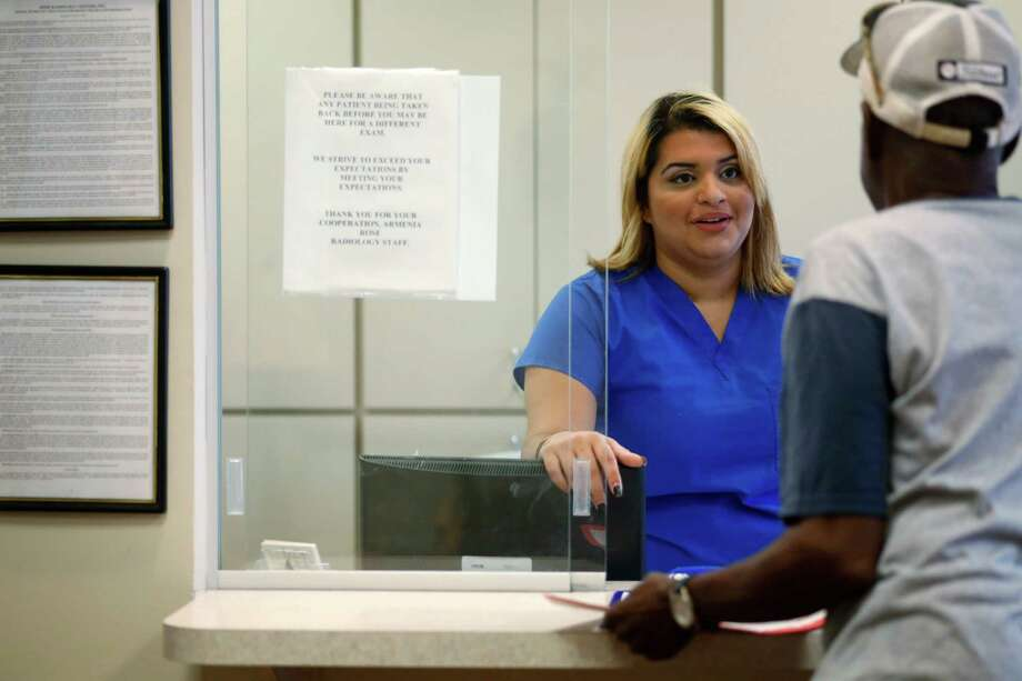 Lizzie Jimenez, 22, of Tampa, talks with a patient Thursday at Rose Radiology in Tampa, Fla. The average family is paying $1,800 less a year because of the Affordable Care Act, according to the nonpartisan Kaiser Family Foundation, and that means the average employer is saving money too. Photo: Monica Herndon /Tampa Bay Times / The Tampa Bay Times