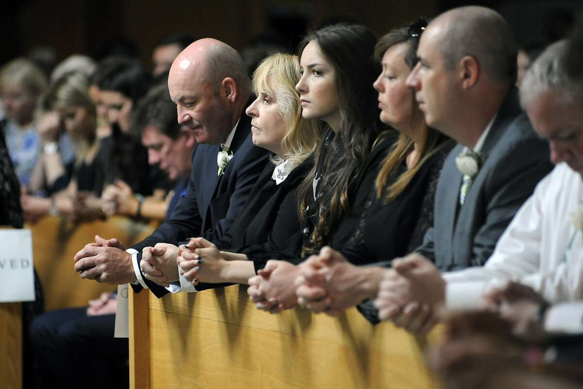 From left, parents George and Jackie Donohoe with their daughter Amanda Donohoe pray during services for Ashley Donohoe, 22, and Olivia Burke, 21 at St. Joseph Catholic Church in Cotati, Calif., on Saturday, June 20, 2015. The two woman were among the several people killed on Tuesday when a balcony snapped off the fifth floor of a Berkeley apartment building during a birthday party. (AP Photo/Michael Short)