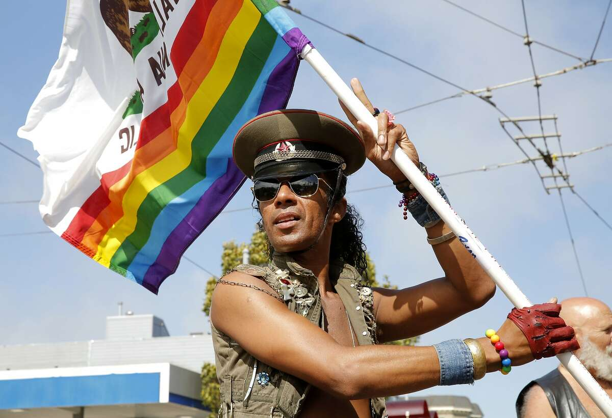 Karicia Ventura stands with a flag of California with a rainbow on the bottom in the Castro neighborhood of San Francisco, California, on Friday, June 26, 2015.