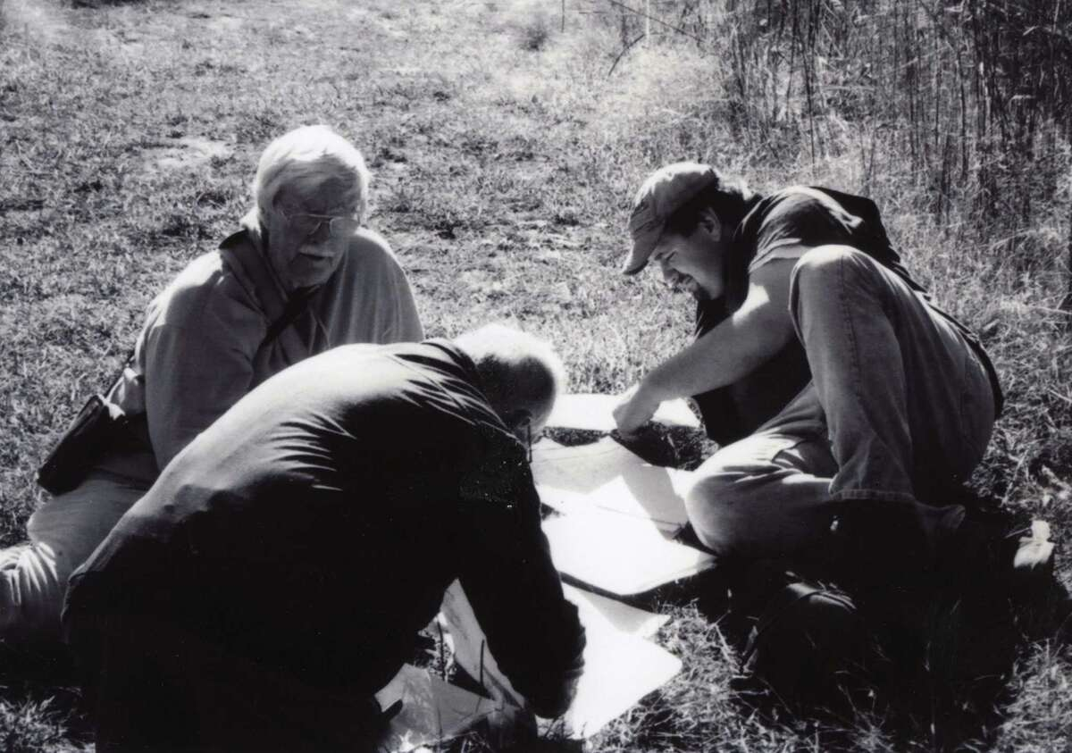 John Wolcott, left, a founding member of Save the Pine Bush, studies maps with Andy Arthur at right and another volunteer. (Daniel Frinta)