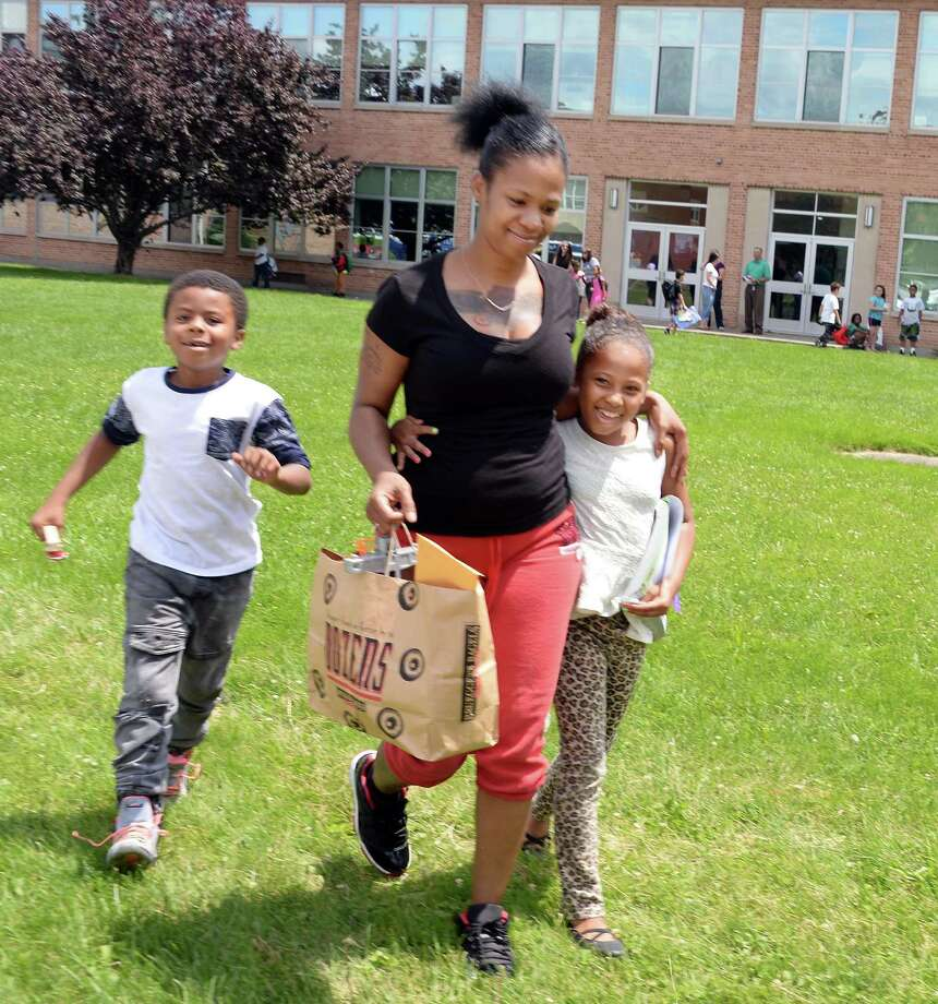 Chrystel Overby with her children Elliot Lopez, 6, left, and Jahlayshia Butler, 8, on last day of the year at Giffen Memorial Elementary School Friday June 26, 2015 in Albany, NY.  (John Carl D'Annibale / Times Union) Photo: John Carl D'Annibale / 00032405A