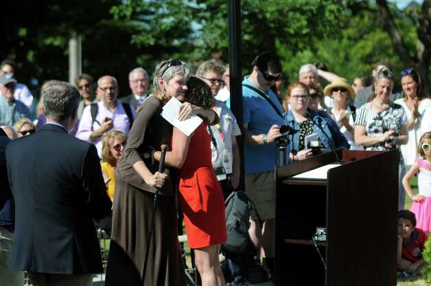 Barbara Glaser, center left, and Kathleen Fyfe, center, both honorary co-chairs of the Spirit of Life and Spencer Trask Memorial Restoration Committee, embrace during the statue's centennial rededication ceremony on Friday, June 26, 2015, at Congress Park in Saratoga Springs, N.Y. (Cindy Schultz / Times Union) Photo: Cindy Schultz / 00032389A