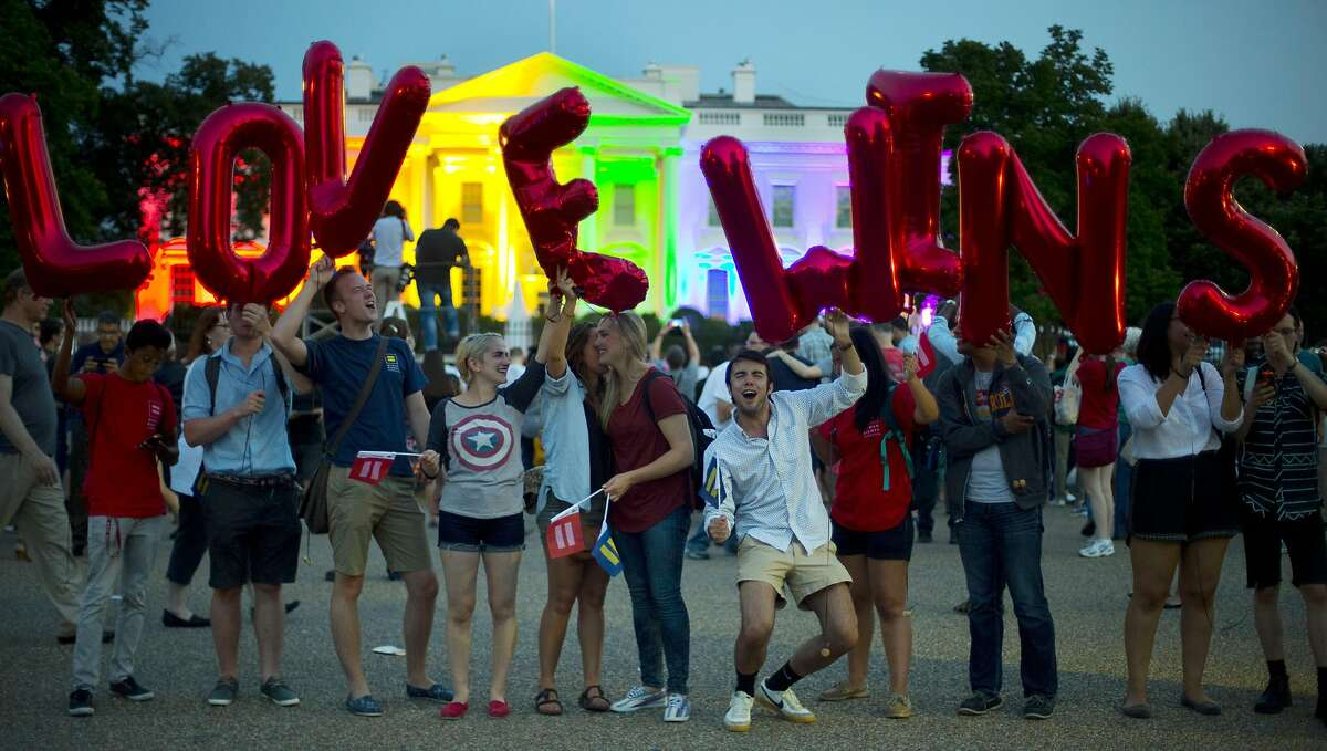 """Same-sex marriage supporters hold up balloons that spell the words """"love wins"""" as they stand in front of the White House, which is lit up in rainbow colors in commemoration of the Supreme Court's ruling to legalize same-sex marriage, on Friday, June 26, 2015, in Washington. Gay and lesbian couples in Washington and across the nation are celebrating Friday's ruling, which will put an end to same-sex marriage bans in the 14 states that still maintain them. (AP Photo/Pablo Martinez Monsivais)"""