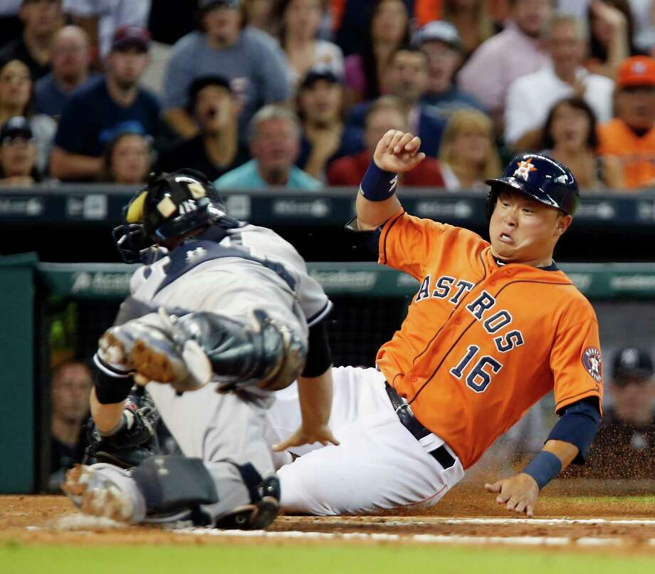 The Astros' Hank Conger, who doubled in the third inning, slides past Yankees catcher Brian McCann to score on a single by Carlos Correa. Photo: James Nielsen, Staff / © 2015  Houston Chronicle
