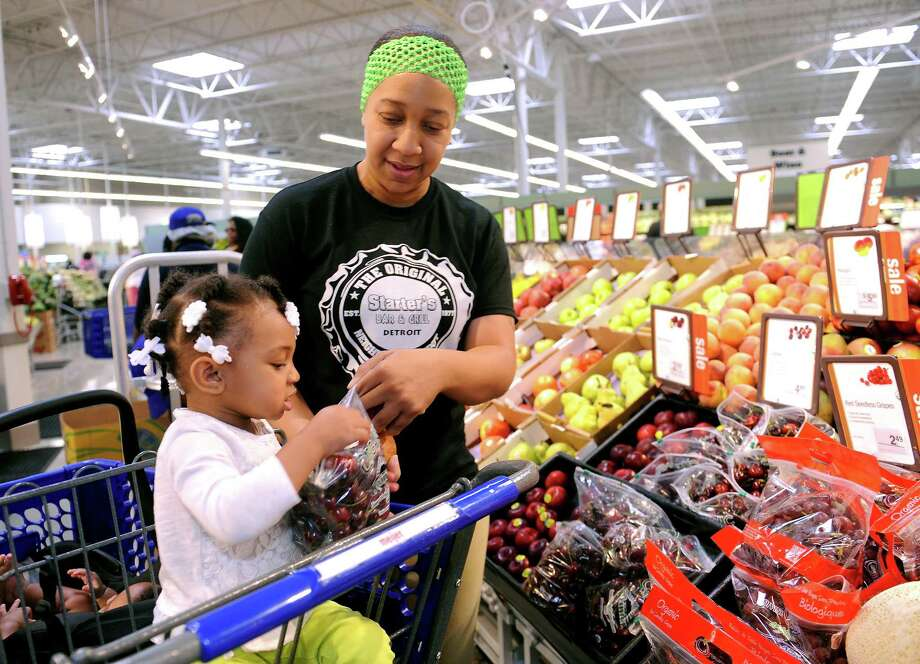In this June 11, 2015, photo, Carmelita Orr, 32, of Detroit, and her 18-month-old daughter, Micheala Meriweather, shop for fresh produce at the new Meijer store, on the site of the old Redford High School, in Detroit. The University of Michigan releases its index of consumer sentiment on Friday, June 26, 2015. (Clarence Tabb Jr./Detroit News via AP)  DETROIT FREE PRESS OUT; HUFFINGTON POST OUT Photo: Clarence Tabb Jr., MBO / Detroit News