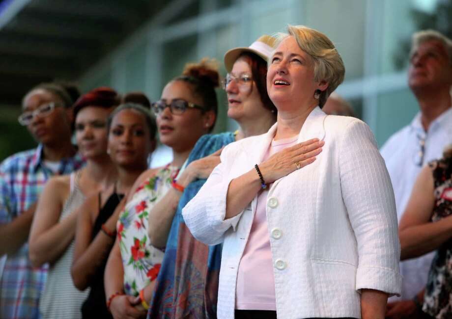 Mayor Annise Parker stands for the Pledge of Allegiance with, from right, wife Kathy Hubbard, daughters Daniela Parker, 24, Marquitta Parker, 20, and Sherry Allen, 20, and daughter's friend Brittany Robinson. Photo: Gary Coronado, Staff / © 2015 Houston Chronicle