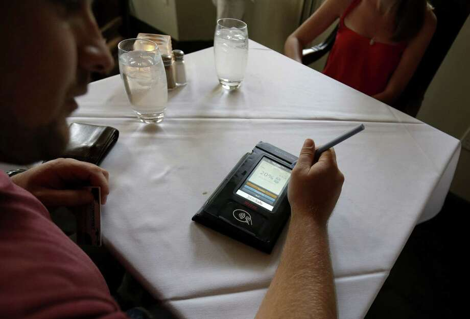 A customer pays his tab with the Rail table-side credit card processing device at Tableau, a Dickie Brennan & Co. restaurant. Dickie Brennan & Co., which operates four New Orleans restaurants, expects to pay over $25,000 to replace its card readers. Photo: Gerald Herbert, STF / AP