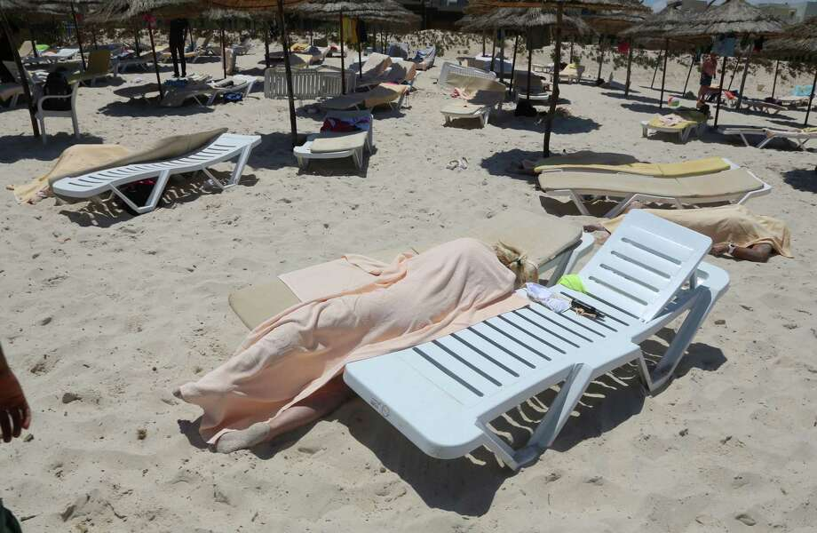 Bodies are covered on a Tunisian beach, in Sousse, Friday June 26, 2015. A young man unfurled an umbrella and pulled out a Kalashnikov, opening fire on European sunbathers in an attack that killed at least 28 people at a Tunisian beach resort — one of three deadly attacks from Europe to the Middle East on Friday that followed a call to violence by Islamic State extremists. (Jawhara FM via AP) ORG XMIT: LON130 Photo: Uncredited / AP