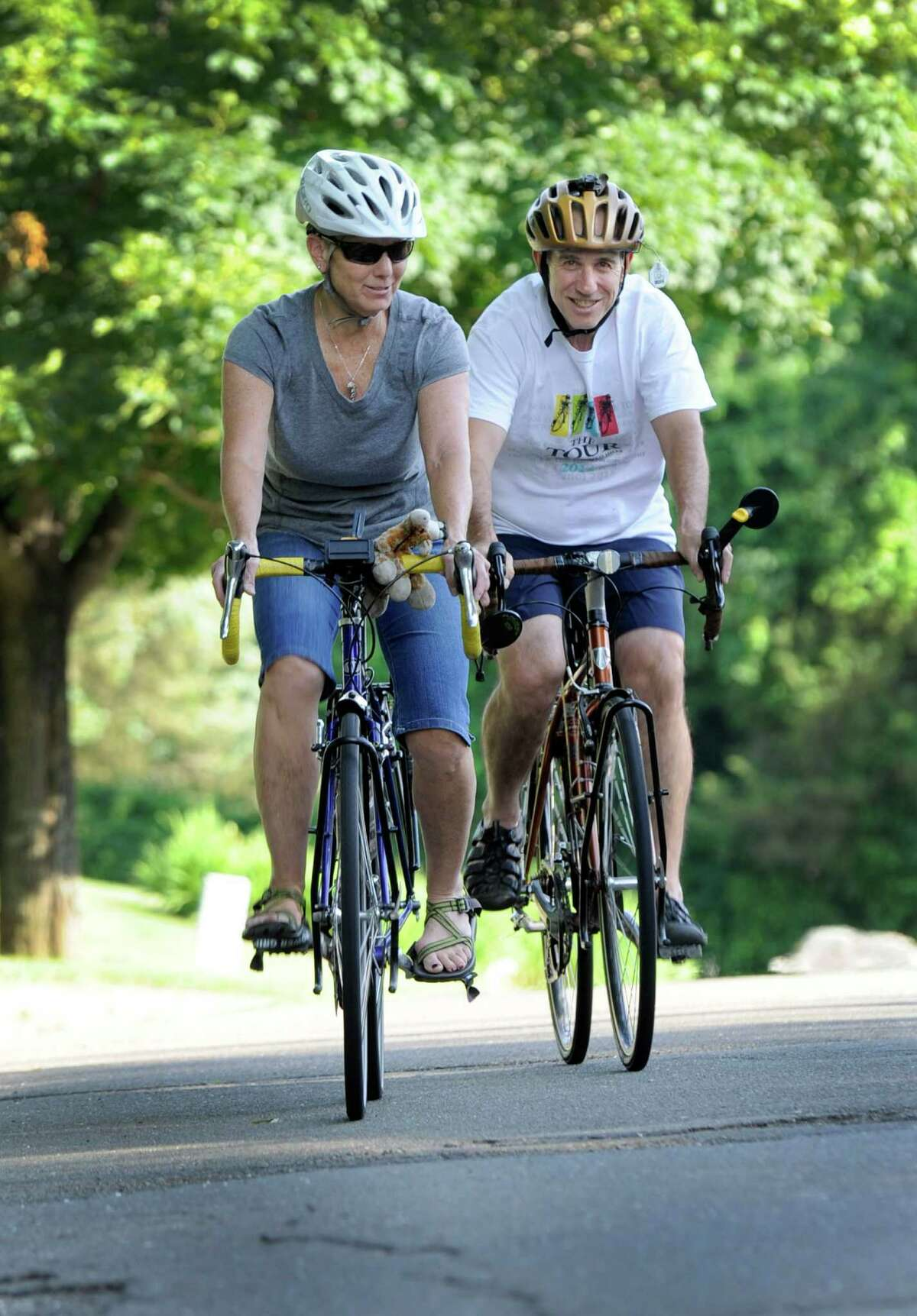 Marti and Dave Fine ride their bicycles in their Danbury neighborhood Thursday, June 25.