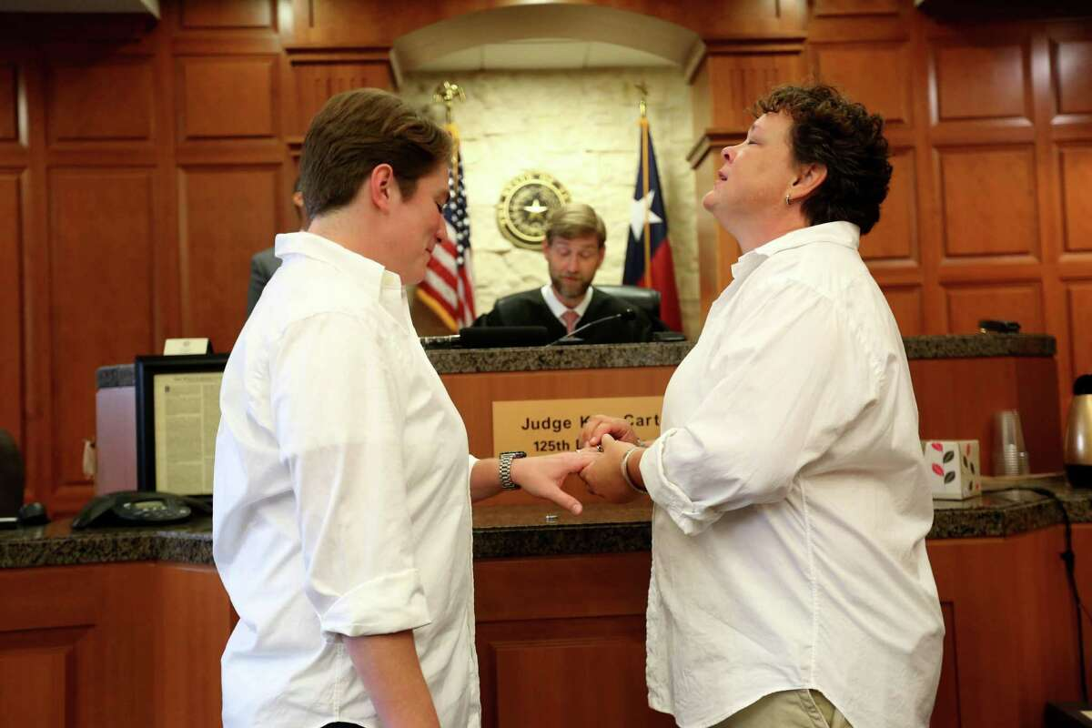 Ashley, left, and Jacquey Creath of Houston, who have been a couple for nine years, are wed by Judge Kyle Carteron Friday.
