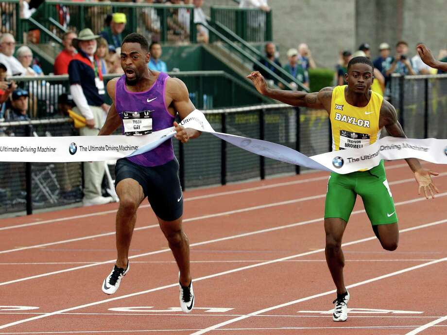 Tyson Gay, left, hits the tape ahead of Trayvon Bromell to win the 100-meter final at the U.S. outdoor track and field championships Friday at Eugene, Ore. Gay was timed in 9.87 seconds. Photo: Don Ryan, STF / AP