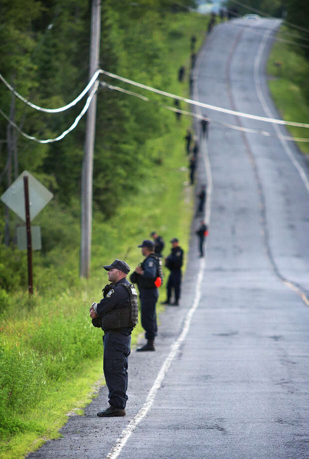 New York State corrections officers line the edge of the forest along County Route 41 in the town of Malone, N.Y. Friday evening, June 26, 2015, while creating a perimeter after Richard Matt was shot and the hunt was on for David Sweat.  Matt, one of two convicted murderers who staged a brazen escape from an upstate maximum-security prison three weeks ago was shot and killed by a Border Patrol agent in a wooded area about 30 miles from the prison on Friday, while Sweat remains on the run.   (Jason Hunter/The Watertown Daily Times via AP)  SYRACUSE OUT ORG XMIT: NYWAT Photo: Jason Hunter / The Watertown Daily Times