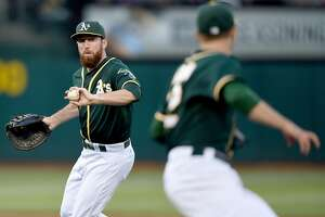 OAKLAND, CA - JUNE 26:  Ike Davis #17 of the Oakland Athletics throws the ball away for an error attempting to get it to pitcher  Jesse Hahn #32 covering first base against the Kansas City Royals in the top of the third inning at O.co Coliseum on June 26, 2015 in Oakland, California. The error allowed Lorenzo Cain #6 to score from third and and Eric Hosmer #35 was safe advancing to second base.  (Photo by Thearon W. Henderson/Getty Images)