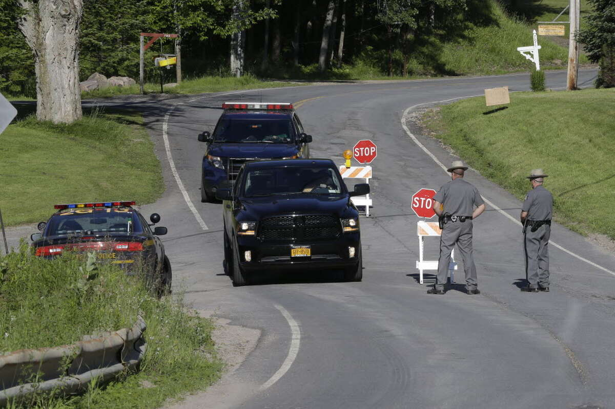 New York State officers stand at the road block at the perimeter of the search area for convicted murderer David Sweat, Saturday, June 27, 2015, in Malone, Convicted murderer Richard Matt was shot and killed by a Border Patrol agent in a wooded area about 30 miles from the Clinton Correctional Facility on Friday. Sweat is on the run, authorities said. (AP Photo/Mary Altaffer)