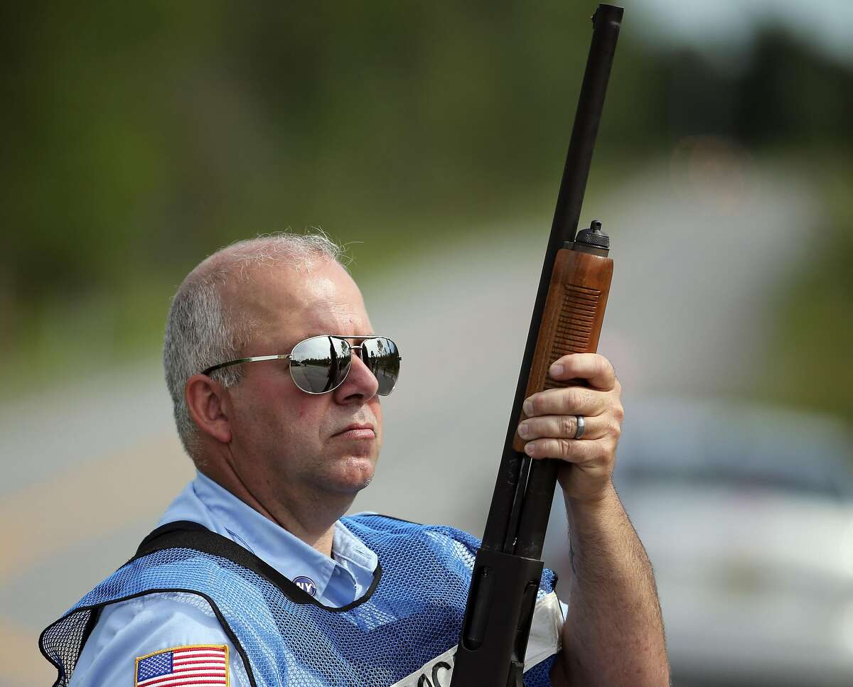 A corrections officer holds a gun at a roadblock on Saturday, June 27, 2015, in Malone, N.Y. The shooting death of Richard Matt, one escaped killer brought new energy to the three-week hunt for David Sweat, a second escaped murderer in the United States as helicopters, search dogs and hundreds of law enforcement officers converged on a wooded area 30 miles from Clinton Correctional Facility. (AP Photo/Mike Groll)