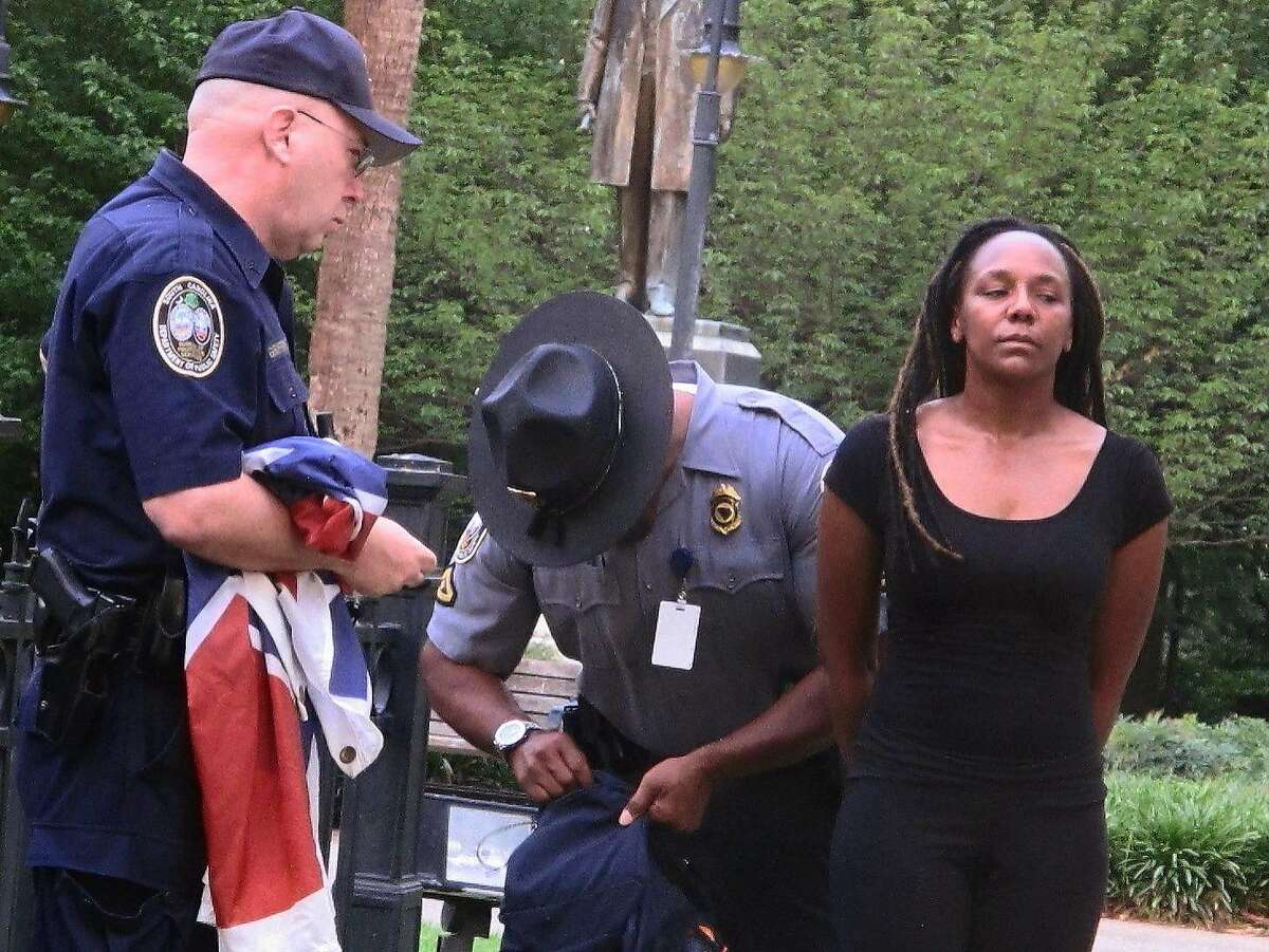Bree Newsome of Charlotte, N.C., right, is taken into custody after she removed the Confederate battle flag from a monument in front of the South Carolina Statehouse in Columbia, S.C., on Saturday, June, 27, 2015. The flag was raised again by capitol workers about 45 minutes later. (AP Photo/Bruce Smith)