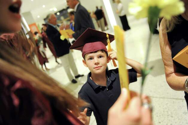 Jackson Bearup, 7, tries on the mortar board of his graduating sister, Chelsea Bearup, at the Colonie High School graduation on Friday, June 26, 2015, at the Empire State Plaza Convention Center in Albany, N.Y. (Cindy Schultz / Times Union) Photo: Cindy Schultz / 00032178A