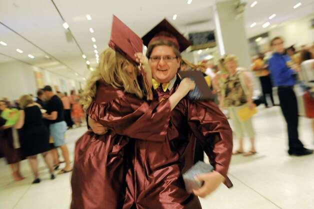 Graduates celebrate the moment as Peter Jones, 18, right, picks up Lexi Love, 17, at the Colonie High School graduation on Friday, June 26, 2015, at the Empire State Plaza Convention Center in Albany, N.Y. (Cindy Schultz / Times Union) Photo: Cindy Schultz / 00032178A