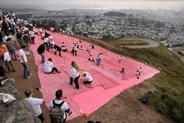 Volunteers scramble across the huge pink triangle during installation atop Twin Peaks, which represents the violence aimed at the LGBT community both in the past and today during Pride Weekend events as seen on Sat. June 27, 2015, in San Francisco, Calif.