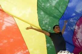 A participant poses underneath a rainbow banner during a gay pride march in Manila on June 27, 2015. Thousands of transgender  people and supporters marched in Manila as part of the Gay Pride March organized by Manila's Lesbian, Gays, Bisexuals, and Transgender (LGBT) organization. AFP PHOTO / NOEL CELISNOEL CELIS/AFP/Getty Images