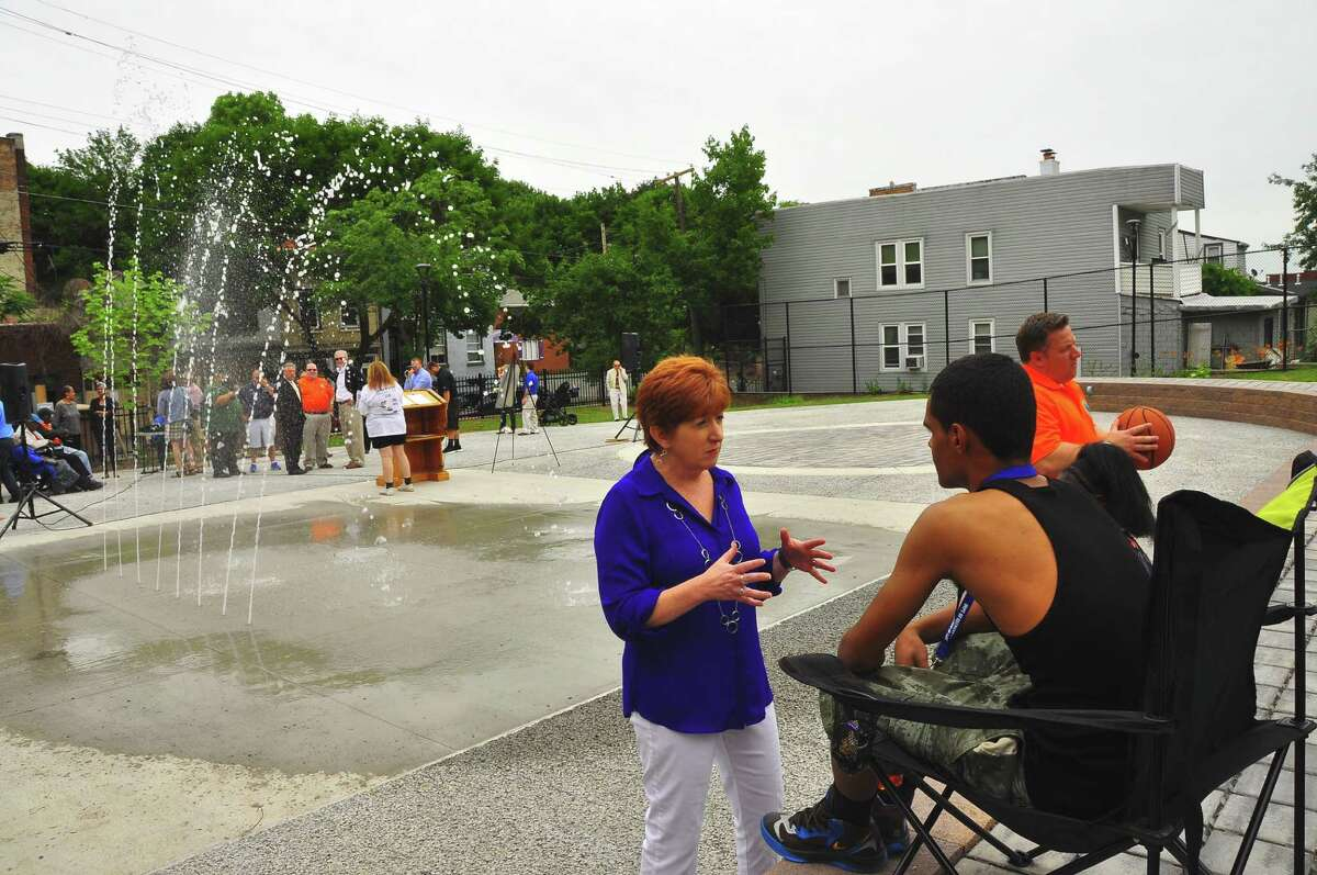 Albany Mayor Kathy Sheehan, center, talks with 15-year-old North Swan Street resident about summer job and recreation opportunities at the newly overhauled North Swan Street Park in Albany on Saturday, June 27, 2015. In the background, with basketball, is Albany County Executive Dan McCoy. (Steve Barnes/Times Union)