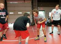 John Kijek, left, a USA wrestling coach and Former University of Iowa wrestling coach and two-time NCAA champion Royce Alger instruck Max Lynch, 14, of Bethel, and David Brancroft, 14, of Brewster during a camp at the Connecticut Wrestling Academy.