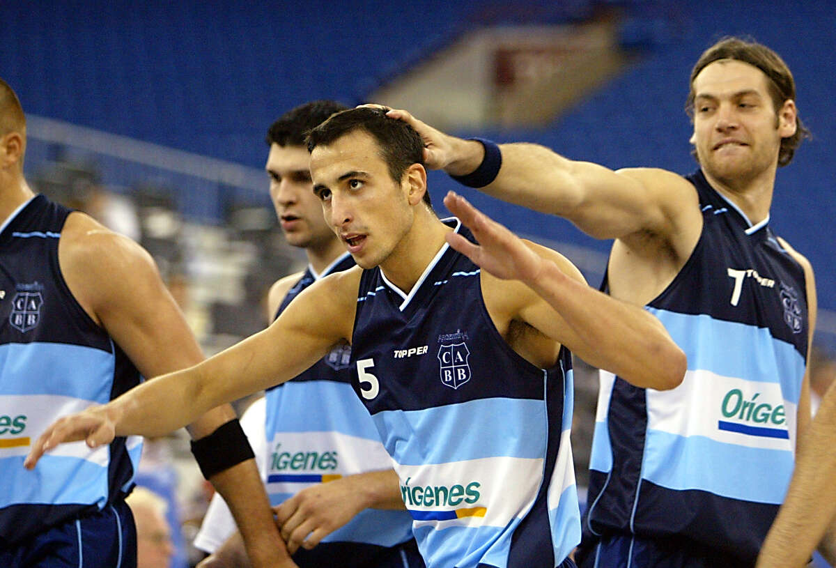 INDIANAPOLIS, UNITED STATES: Emanuel Ginobili (C) of Argentina is greeted by teammate Fabricio Oberto (R) after a three point basket against New Zealand 31 August, 2002 during the second half of their preliminary round one game of the 2002 Men's FIBA World Basketball Championships at the RCA Dome in Indianapolis, IN. Argentina won the game 112-85. AFP PHOTO/Jeff HAYNES (Photo credit should read JEFF HAYNES/AFP/Getty Images)