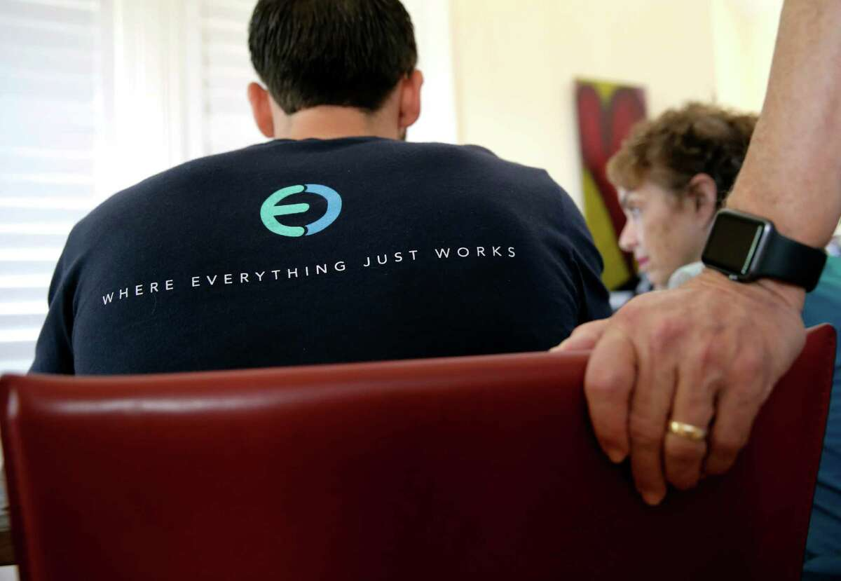 Co-founder and CEO of Eden, (back) wears a company tee shirt during a visit to the home of clients David and Abby Ross in Palo Alto, Calif. on Thurs. June 25, 2015. Eden is an on-demand service where Eden Tech Wizards visit customers exactly when and where they are needed, to solve consumer's technology needs.