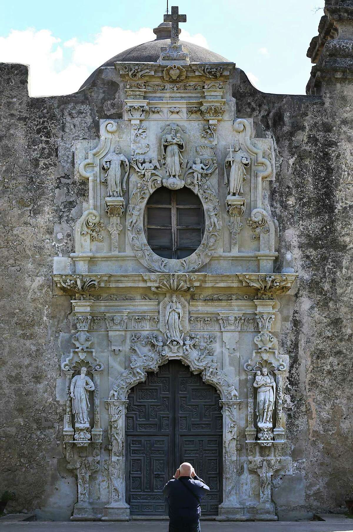 A tourist take a picure of the facade at Mission San Jose. Thursday, Feb. 19, 2015.