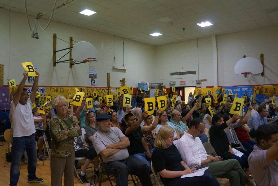 New Lebanon School parents hold up signs in support of the Scheme B building plan, during a forum Tuesday night at the elementary school. Photo: Paul Schott / Paul Schott / Greenwich Time