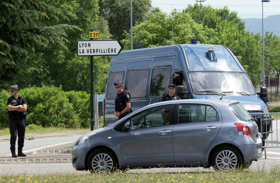 Police officers guard the road leading to a plant in Saint-Quentin-Fallavier, southeast of Lyon, France, Saturday, June 27, 2015, where an attack took place yesterday June 26. A spokeswoman for the Paris prosecutor's office says one of the four suspects detained over an explosion and beheading in southeast France has been released, while the suspected assassin isn't speaking to investigators. (AP Photo/Michel Euler) Photo: Michel Euler, STF / AP
