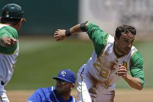 Oakland Athletics' Sam Fuld, right, runs to score past Kansas City Royals third baseman Mike Moustakas, center, in the first inning of a baseball game Saturday, June 27, 2015, in Oakland, Calif. Fuld scored after stealing third base on a throwing error by Royals' Chris Young. (AP Photo/Ben Margot)