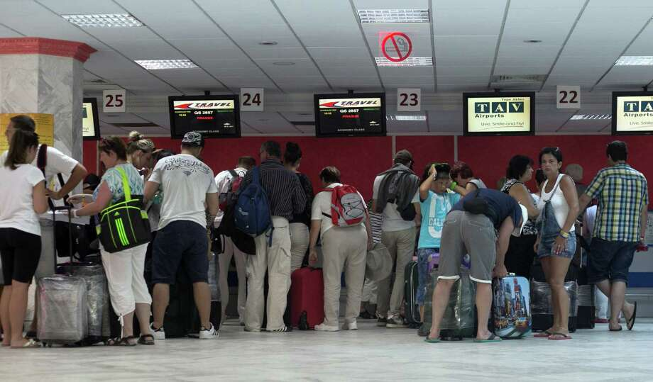 Tourists line up at Monastir airport as they prepare to leave Tunisia, a day after a shooting attack which took place in the coastal town of Sousse Saturday, June 27, 2015. Tunisia's prime minister announced on Saturday a string of new security measures including closing renegade mosques and calling up army reservists as thousands of tourists fled the North African country in wake of its worst terrorist attack ever. Tourists crowded into the airport at Hammamet near the coastal city of Sousse where a young man dressed in shorts on Friday pulled an assault rifle and grenades out of his beach umbrella and killed 38 people, mostly tourists. (AP Photo/Leila Khemissi) Photo: Leila Khemissi, STR / AP
