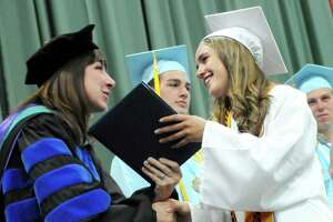 Class president Rachel Mydosh, center, receives her diplomas from Superintendent Angela Nagle, left, during the Columbia High commencement ceremony on Saturday, June 27, 2015, at Hudson Valley Community College in Troy, N.Y. (Cindy Schultz / Times Union)