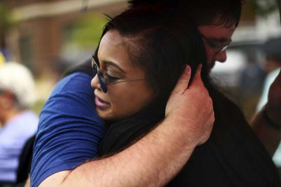 Jordan Black and James Wooldridge hug during at a joint service for Tywanza Sanders and Susie Jackson, two relatives among the nine shot dead, at the Emanuel A.M.E. Church in Charleston, S.C., June 27, 2015. Survivors say Sanders tried to talk the gunman out of his attack on June 17, then tried to shield his aunt with his own body.  (Travis Dove/The New York Times)