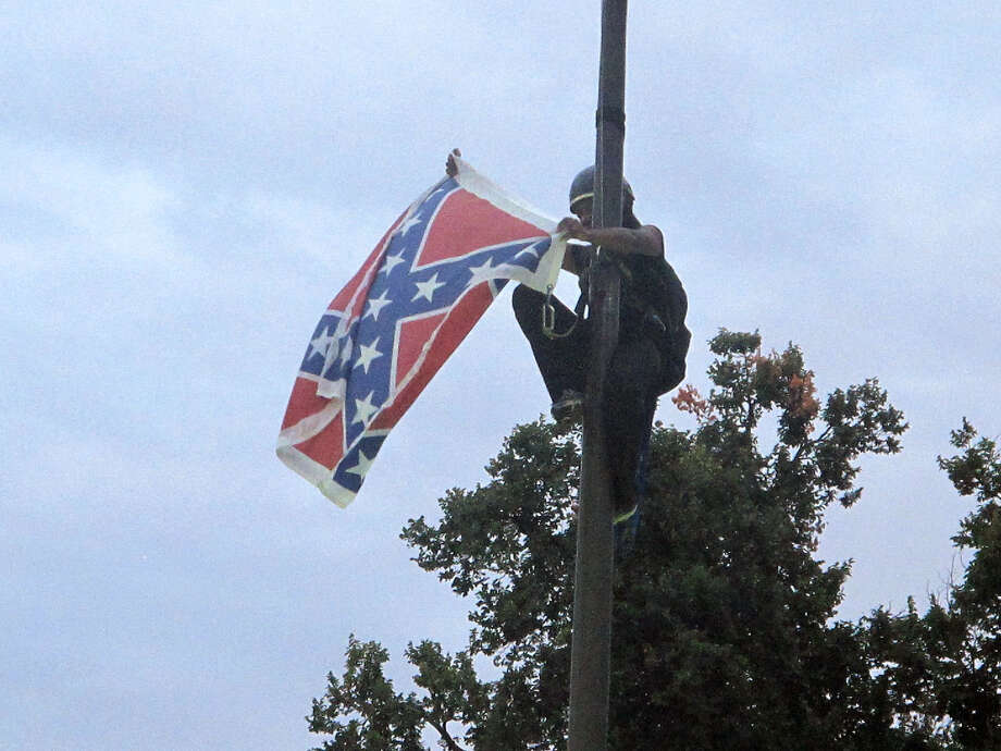 Bree Newsome of Charlotte, N.C., removes the Confederate battle flag at a Confederate monument at the Statehouse in Columbia, S.C., on Saturday, June, 27, 2015. She was taken into custody when she came down. The flag was raised again by capitol workers about 45 minutes later.  (AP Photo/Bruce Smith) ORG XMIT: SCBS103 Photo: Bruce Smith / AP