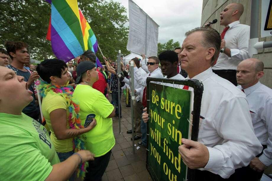 Anti-gay marriage protestors picket at the Cincinnati Pride festival at Riverside Park, Saturday, June 27, 2015, in Cincinnati. On Friday, June 26, 2015, the U.S. Supreme Court legalized gay marriage nationwide. (AP Photo/John Minchillo) ORG XMIT: OHJM110 Photo: John Minchillo / AP