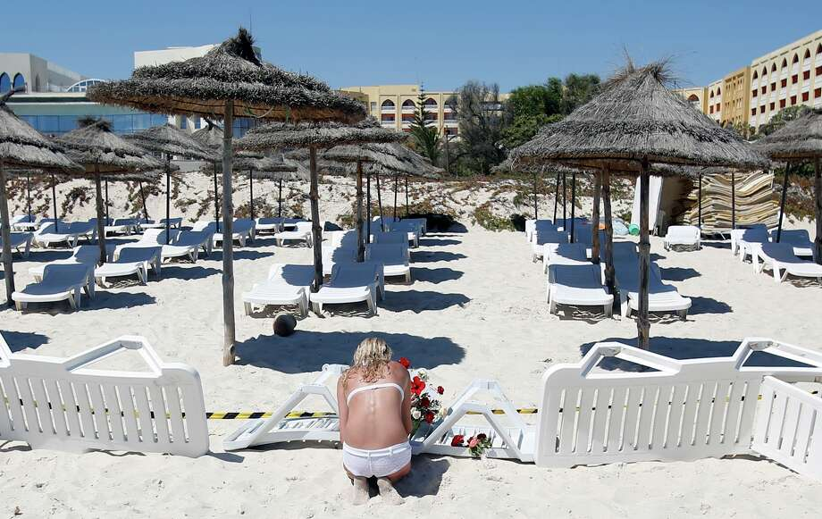 A young woman lays flowers at the scene of a shooting in Sousse, Tunisia, Saturday, June 27, 2015. The morning after a lone gunman killed at tens of people at a beach resort in Tunisia, busloads of tourists are heading to the nearby Enfidha-Hammamet airport hoping to return to their home countries. (AP Photo/Darko Vojinovic) ORG XMIT: XDMV232 Photo: Darko Vojinovic / AP